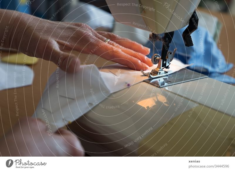 Hände an der Nähmaschine halten den zusammengesteckten Stoff und nähen Futterstoff für einen Mundschutz zusammen / corona thoughts Handarbeit Schneidern Mode