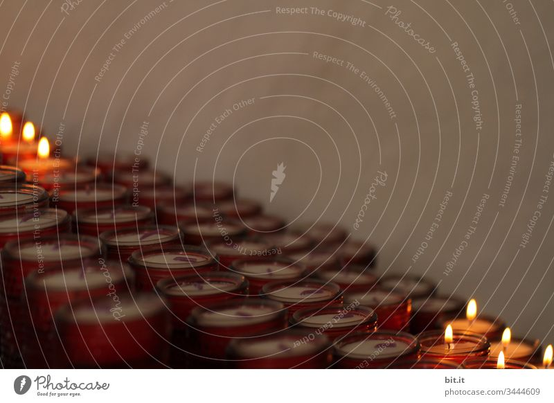 Brennende, leuchtende Kerzen in einem Opferstock in der Kirche, vor einer grauen Wand in trauriger Stimmung. Schwache Tiefenschärfe Lichterscheinung