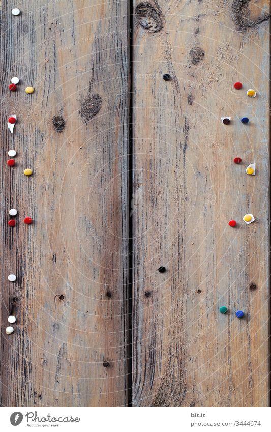 Viele, bunte Reissnägel stecken an einem leeren, alten Holzbrett. Wand Brett Schwarzes Brett trashig Abnutzung Zahn der Zeit Heftklammer trist Information
