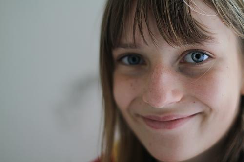 Weiblicher, glücklicher Teenager mit blauen Augen und Pony, lächelt positiv, glücklich und optimistisch mit grinsendem Mund und Lebensfreude, vor grauem Hintergrund, in den Tag.
