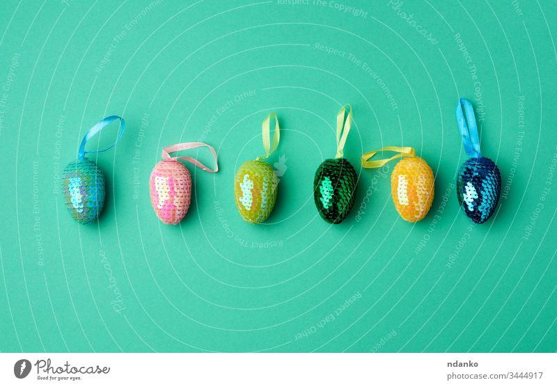 mehrfarbige dekorative Ostereier mit Pailletten auf grünem Hintergrund Ostern Dekoration & Verzierung Feiertag Frühling Ei traditionell Symbol farbenfroh Saison