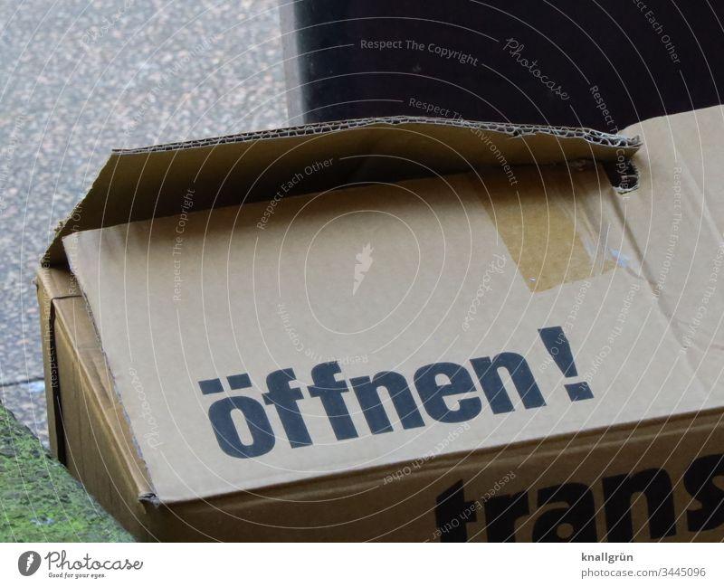 Brauner Pappkarton mit der Aufschrift öffnen! Karton Pappe Kommunizieren Sprache Buchstaben Typographie Schriftzeichen Lateinisches Alphabet Wort Letter
