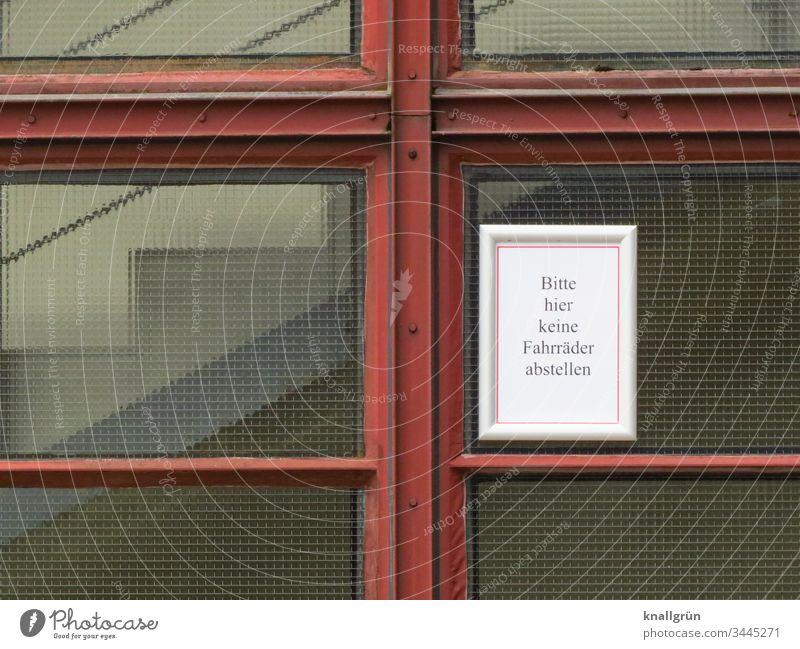 """Hinweisschild """"Bitte hier keine Fahrräder abstellen"""" angebracht an einer Drahtglasscheibe eines Treppenhauses Verbotsschild Kommunizieren Verständigung"""