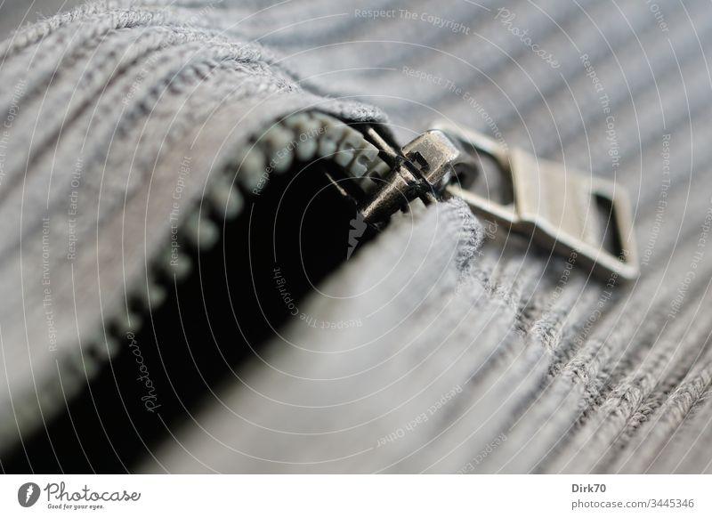 Makroaufnahme eine Reißverschlusses an einem grauen Pullover gestrickt strickwaren Troyer Bekleidung Kleidung kleidungsstück geringe Tiefenschärfe