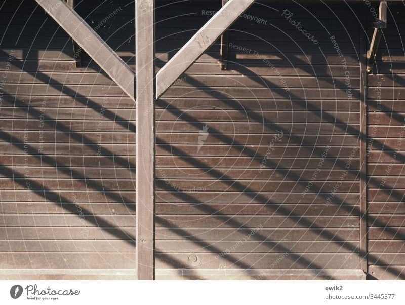 Y Holz Wand Bungalow Pfosten Pfeiler diagonal Schatten Schattenwurf einfach Holzwand Sonnenlicht Strukturen & Formen braun Gedeckte Farben Muster Detailaufnahme