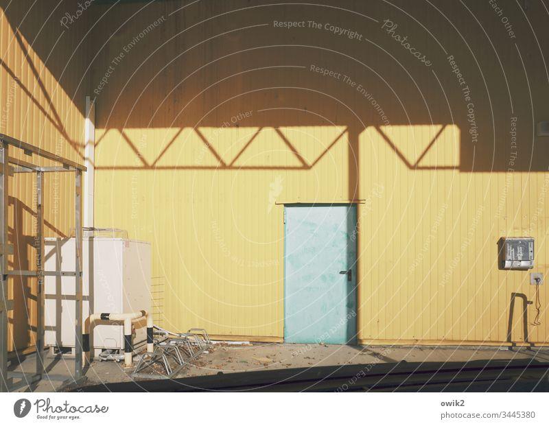 Hintertürchen Baumarkt Wand Metall Blech Blechwand gelb Dach Schatten Sonnenlicht Kontrast Tür abgenutzt Außenaufnahme Farbfoto Menschenleer Tag Detailaufnahme