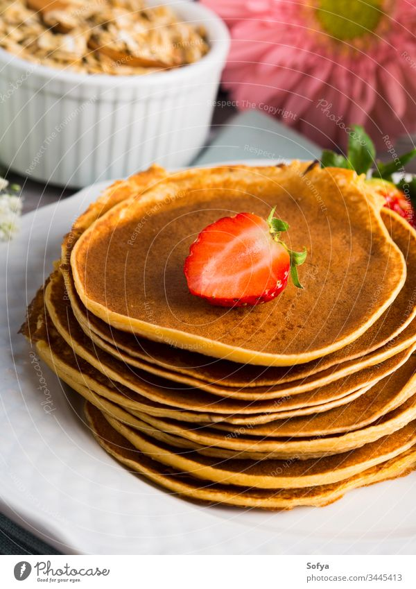 Stapel von Haferflocken-Pfannkuchen mit Erdbeeren Gesundheit Beeren Sommer Frühling Koch Blume Frühstück Morgen Mehl Sirup Ahorn Speise Teller weiß Tisch