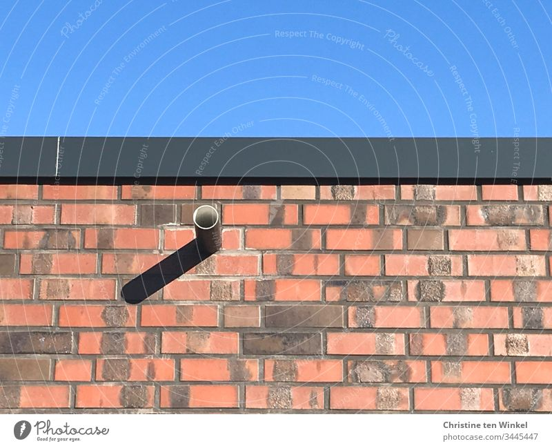 rote Klinkerfassade mit Regenabfluss und Schatten gegen blauen Himmel Mauer Fassade Verblender blauer Himmel Licht und Schatten Sonnenlicht Wand Haus Gebäude