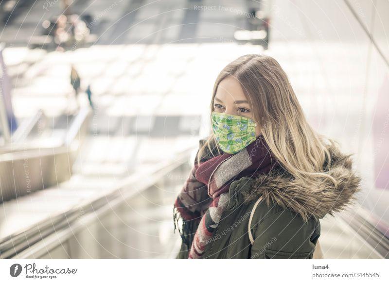 junge Frau mit Mundschutz in der Stadt Maske Atemschutzmaske Schutzmaske Virus Coronavirus besorgt Viren Pandemie Ansteckung bedrohlich Grippe anstecken