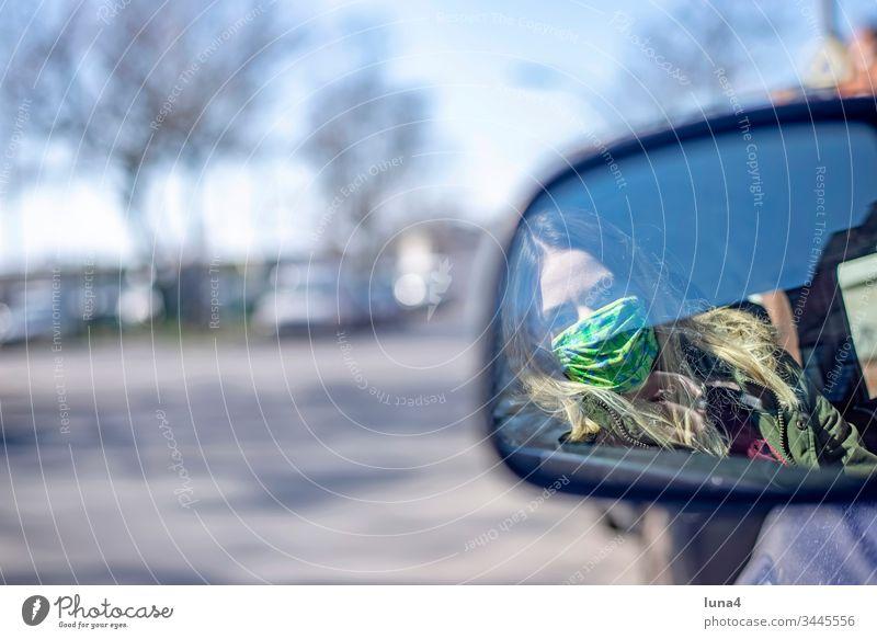 junge Frau mit Mundschutz sitzt im Auto Maske Rückspiegel Spiegel nachdenklich fahren Atemschutzmaske Pkw Schutzmaske Stadt Virus Coronavirus besorgt Viren