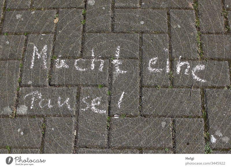 Macht eine Pause!  - mit weißer Kreide geschrieben auf grauen Pflastersteinen Schrift Buchstaben Wort Satz Schriftzeichen Text menschenleer Gehweg Kommunikation