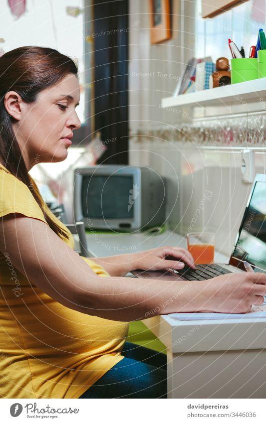 Frau, die von zu Hause aus mit einem Laptop arbeitet schwanger von zu Hause aus arbeiten Coronavirus Seuche Einsperrung Risikogruppe zu Hause bleiben Küche