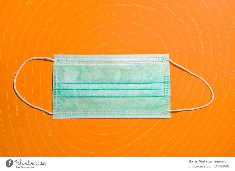 medizinische Maske, isoliert auf orangem Hintergrund zum Schutz vor dem Coronavirus covid-19 Atemschutzmaske Amerikaner Business Kapital China Konzept