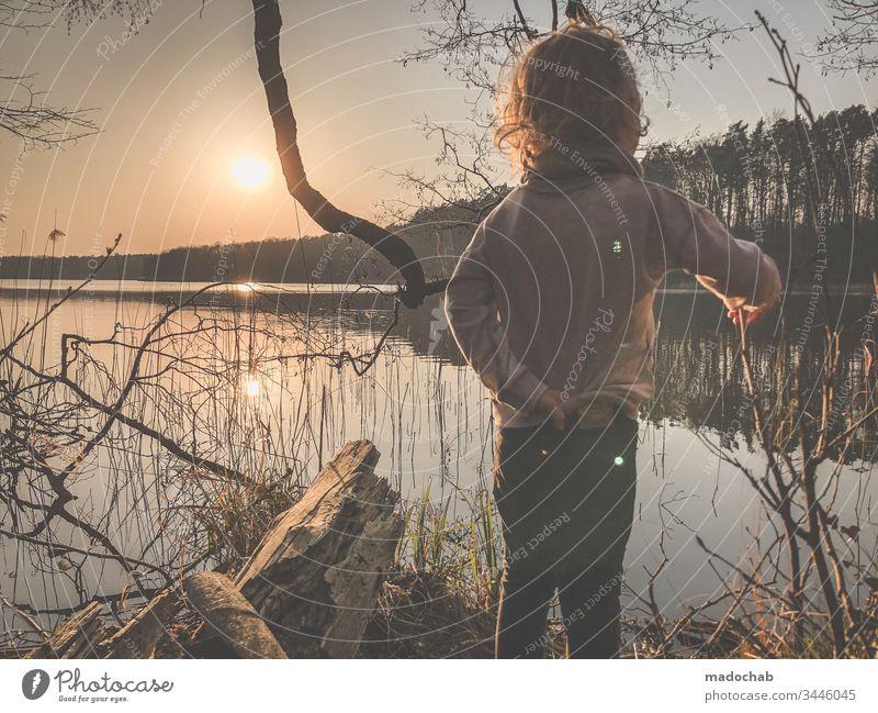 Kind steht beim Sonnenuntergang am Seeufer und blickt in die Zukunft Wasser sonne Natur Wald Junge Sonnenlicht Gegenlicht romantidch Dämmerung Landschaft Umwelt