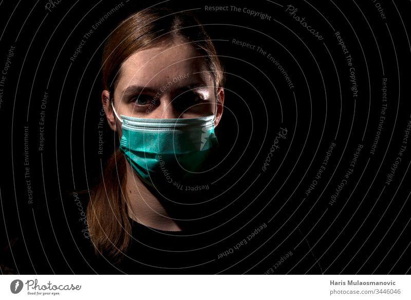 Frau mit medizinischer Maske zum Schutz des Coronavirus covid-19 SARS-CoV-2, Frau mit Maske auf schwarzem Hintergrund 30s Erwachsener apokalyptisch