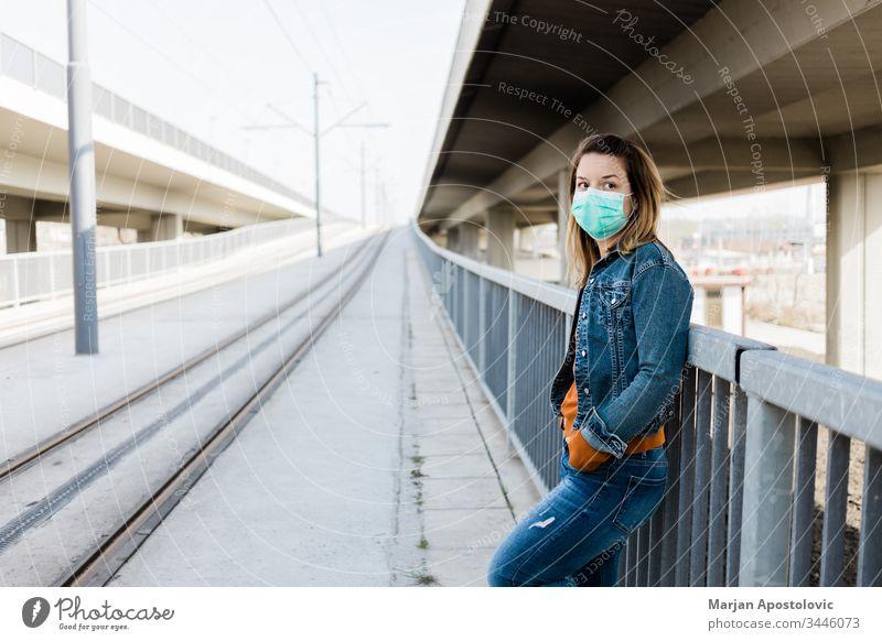 Junge Frau mit einer chirurgischen Maske in einer leeren Straßenbahnhaltestelle allein Biogefährdung Pflege Kaukasier Großstadt Ansteckung Coronavirus covid-19