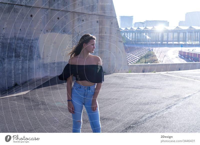 Eine junge schöne Frau mit langen Haaren steht auf der Promenade und schaut nachdenklich in die Kamera im Freien posierend Lifestyle attraktiv hübsch 1 Gedanken