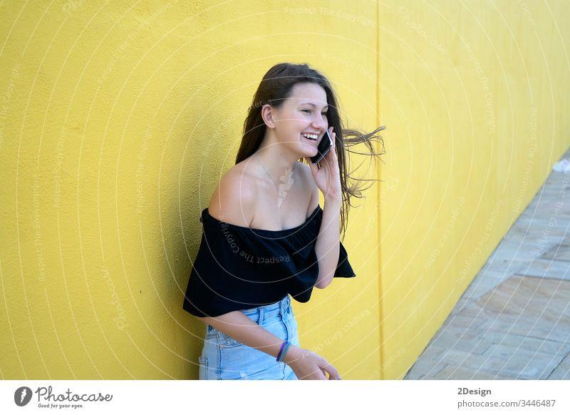 Hübsches Mädchen an gelber Wand lehnt, junge freundliche Frau lächelt glücklich an einem sonnigen Sommertag 1 Person Erwachsener attraktiv Glück Hintergrund