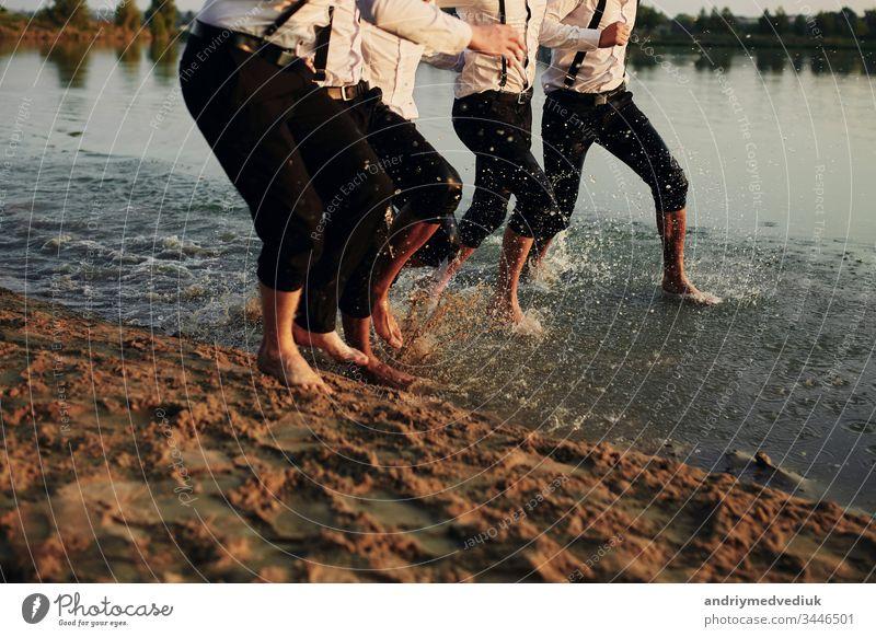 Männerfüße im Wasser. Männer in Kostümen laufen auf dem Wasser. Sie haben Spaß, spielen und spritzen Wasser um sich herum. Sommer. Gruppe glücklicher junger Männerfüße spritzen Wasser im Meer und spritzen am Strand