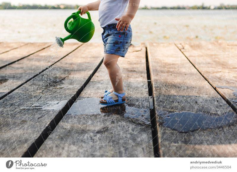 Ein kleines Mädchen spielt mit der Gießkanne einer Holzbrücke. Frühling und Sommer. Gartenarbeit. grüne Gießkanne Bewässerung Dose Wasser Baby wenig Kind