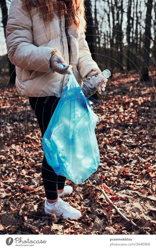 Junge Frau räumt einen Wald auf. Freiwillige Helferin beim Einsammeln von Plastikmüll in Säcke. Konzept der Plastikbelastung und zu viel Plastikabfall. Umweltproblematik. Umweltschäden. Verantwortung für die Umwelt. Echte Menschen, authentische Situationen