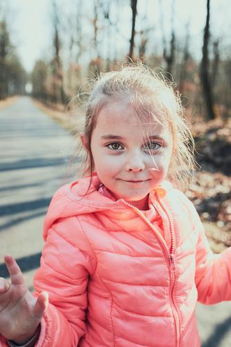Porträt eines kleinen Mädchens, das im Park spielt und sich an einem sonnigen Herbsttag amüsiert. Echte Menschen, authentische Situationen Kind Spielen Spaß