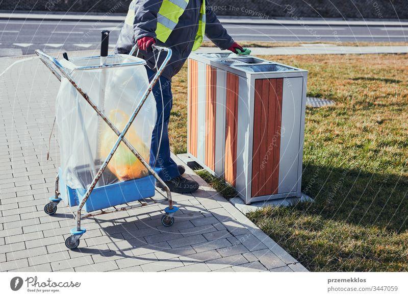 Reinigungskraft beim Ausleeren des Mülls. Mann mit gelber Weste, der einen Behälter reinigt, steht neben einem Reinigungswagen. Echte Menschen, authentische Situationen