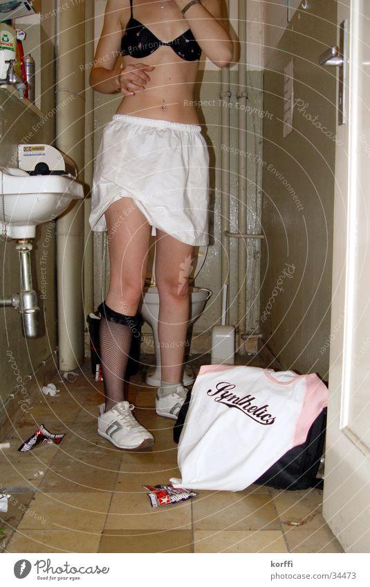toilette eins Frau Toilette 1 entkleiden T-Shirt BH außergewöhnlich stehen