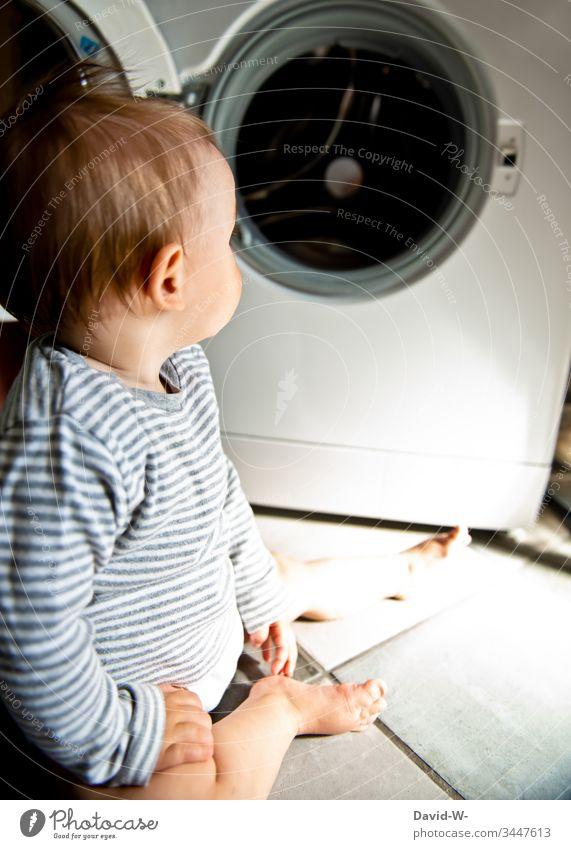 Baby Kleinkind sitzt interessiert und neugierig vor Waschmaschine auf dem Boden niedlich Kind Gefahr beobachten neugierde Junge Verantwortung erkunden erkundend