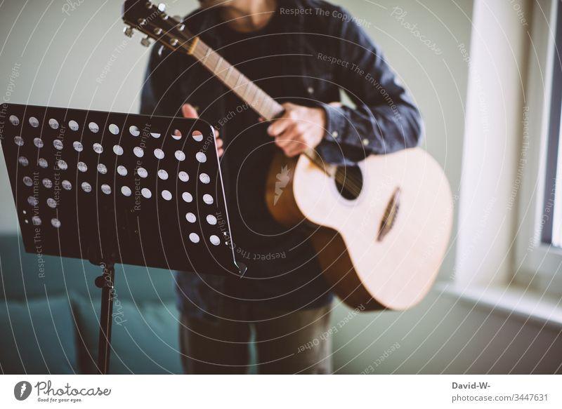 Gitarrist Gitarre Gitarrenspieler Notenständer zu Hause üben Übung übend lernen fleiß Motivation Lehrer Schüler Unterricht Notenpult Bildung Schule