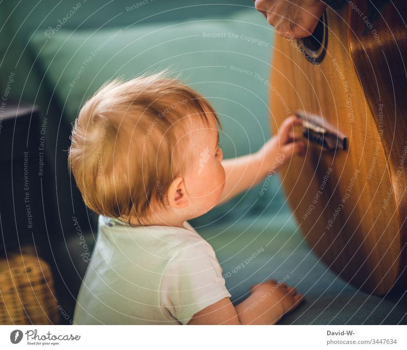 Kleinkind berührt Instrument Gitarre und lernt etwas Neues Kind Werkzeug lernen musikalische Früherziehung Musik musizieren Musiker niedlich beeindruckt zupfen
