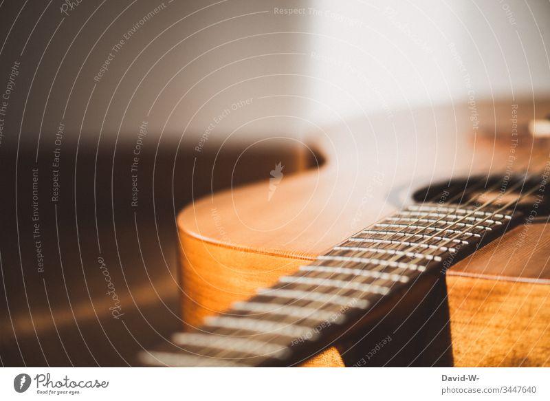 Gitarre Musikinstrument liegt auf dem Boden und wird vom Sonnenlicht angestrahlt liegen fußboden Pause Auszeit Textfreiraum oben Schatten Licht