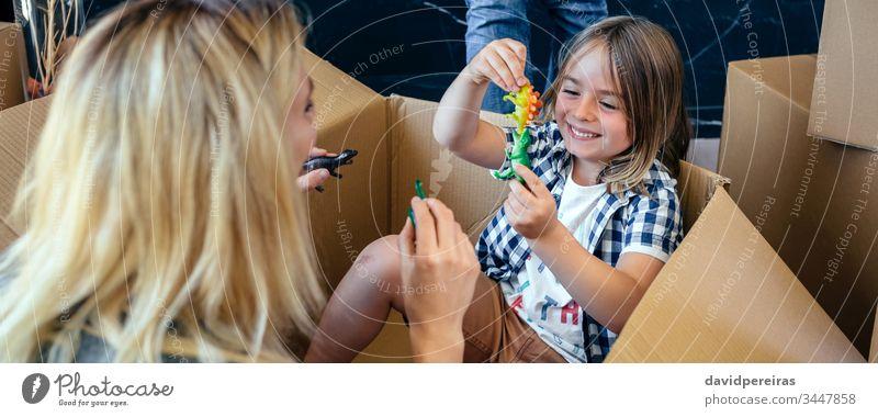 Mutter und Sohn spielen in einem Pappkarton Coronavirus Einsperrung panoramisch Spaß Spielen Dinosaurier Kasten Karton Quarantäne Kopfball zu Hause bleiben
