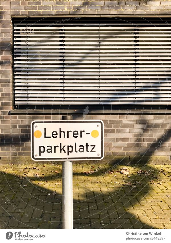 Leerer Parkplatz. Ein Schild 'Lehrerparkplatz' vor einem Schulgebäude mit geschlossenen Rollläden Hinweisschild Schilder & Markierungen Schriftzeichen
