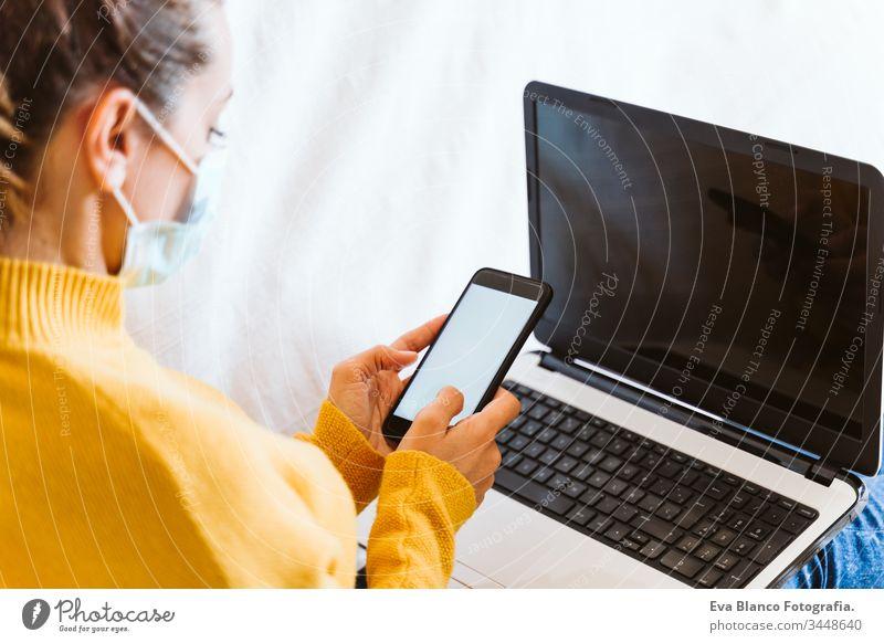 """junge Frau, die zu Hause am Laptop arbeitet, auf der Couch sitzt und eine Schutzmaske trägt. Das Konzept """"zu Hause bleiben"""" während des Coronavirus covid-2019"""