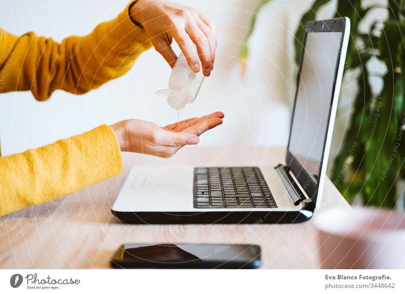 junge Frau, die zu Hause am Laptop arbeitet und Handdesinfektionsmittel Alkoholgel verwendet. Während des Coronavirus covid-2019-Konzepts zu Hause bleiben