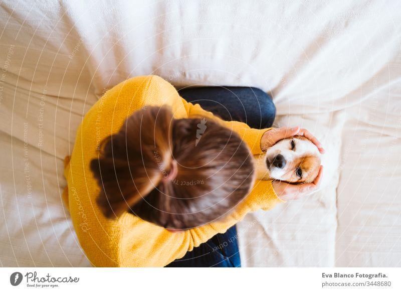 """junge Frau, die zu Hause ihren niedlichen kleinen Hund umarmt, auf der Couch sitzt und eine Schutzmaske trägt. Konzept """"Zuhause bleiben"""" während Coronavirus covid-2019"""
