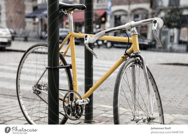 Gelbes Vintage-Rennrad mit Bügelschloss an Straßenschild angeschlossen Fahrrad Retro Tour de France Chrom Stahlrohl Pedale Kette Ritzel Rad Reifen Mantel Bremse