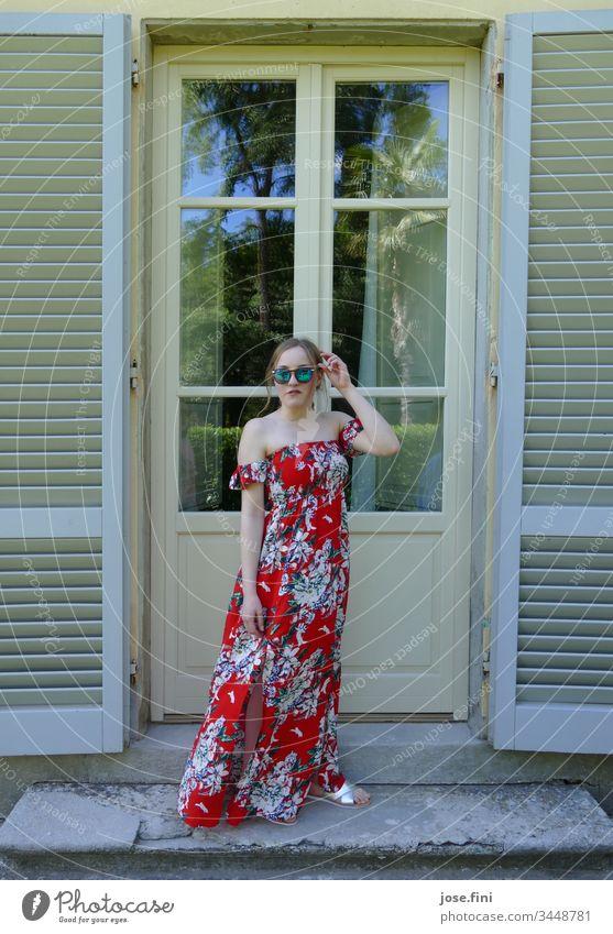 junge Frau steht in langem Sommerkleid und Sonnenbrille vor einer Altbau-Tür mit offenen Holzrollläden Junge Frau blond Schlank feminin schön hübsch Mode