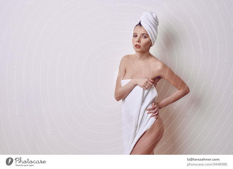 Verlockende junge nackte Frau, die ihre Brüste und die Vorderseite ihres Oberkörpers mit einem frischen, sauberen weißen Handtuch bedeckt, während sie mit schwülerem Ausdruck und geteilten Lippen über einen weißen Studiohintergrund in die Kamera schaut