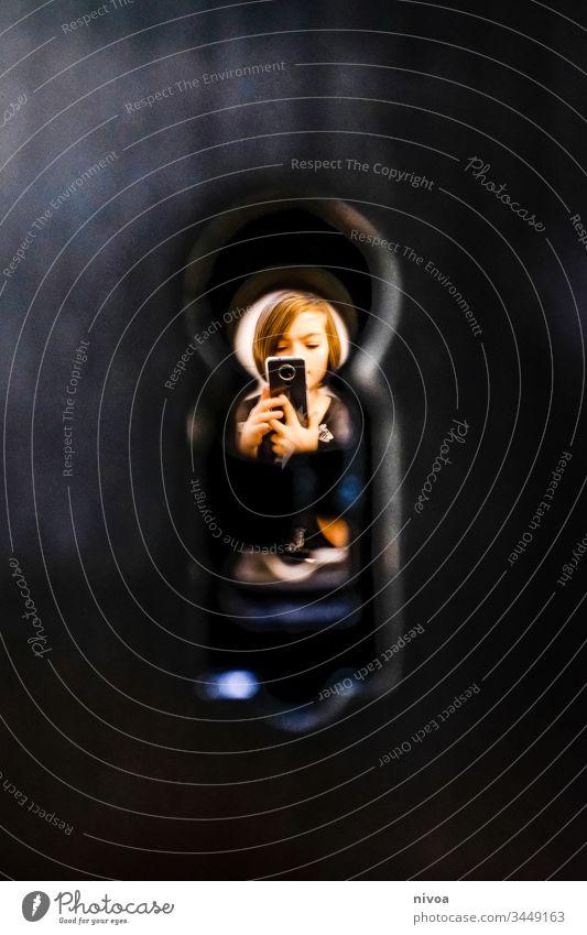 junge durchs schüsselloch Junge Schlüsselloch Handy Spielen beobachten spionieren Textfreiraum links Detailaufnahme Farbfoto Innenaufnahme Blick Mensch Auge