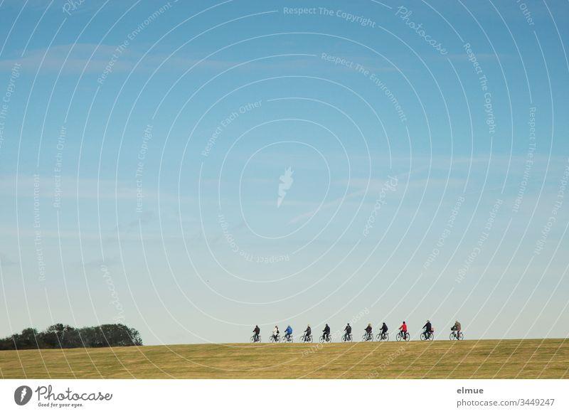 11 Radfahrer fahren hintereinander auf einem Damm radfahren Gruppe elf schönes Wetter Himmel himmelblau Abstand Ausflug Sport Außenaufnahme Gesundheit Natur