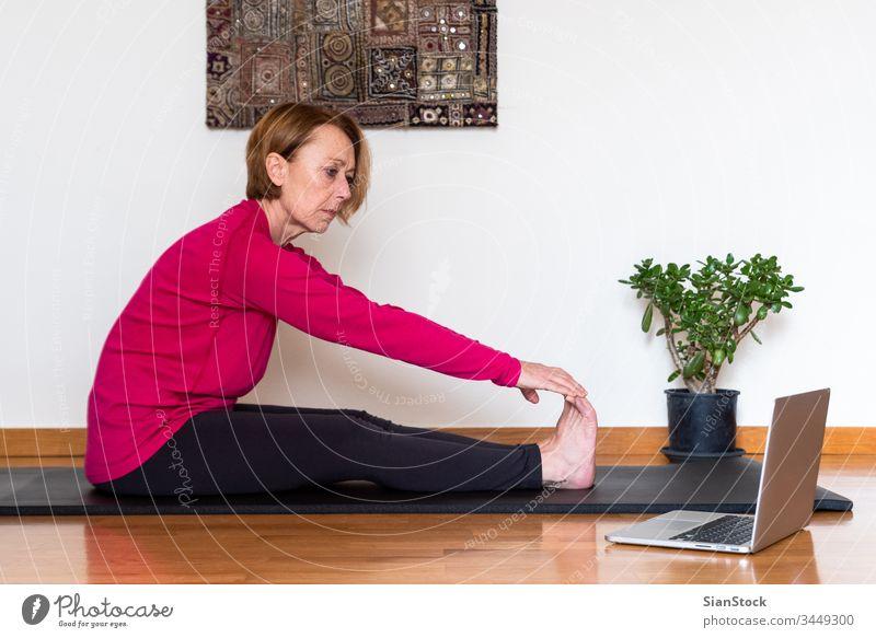 Frau mittleren Alters sieht sich auf ihrem Laptop ein Online-Video-Tutorial mit Yoga-Übungen an. Konzept Yoga zu Hause. Biegen Schönheit Training Europäer