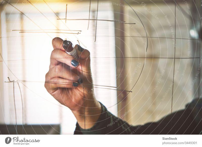 Hand einer Geschäftsfrau, die im Büro auf Glastafel schreibt Holzplatte schreibend Hände Zeichnung Business Markierung Person Bildschirm Menschen weiß