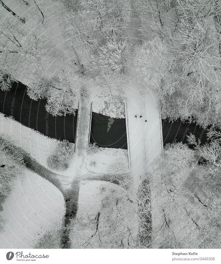 Eine schneebedeckte Brücke, auf der Menschen hoch oben in einer kalten Winterlandschaft spazieren gehen. Schnee laufen vertikal Dröhnen Antenne Baum Fluss