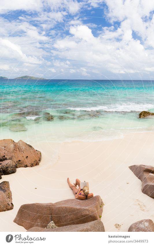 Frau liest Buch über den bildschönen Strand Anse Patates auf der Insel La Digue, Seychellen. reisen lesen Sommer Urlaub Lifestyle Feiertag MEER Sand Resort