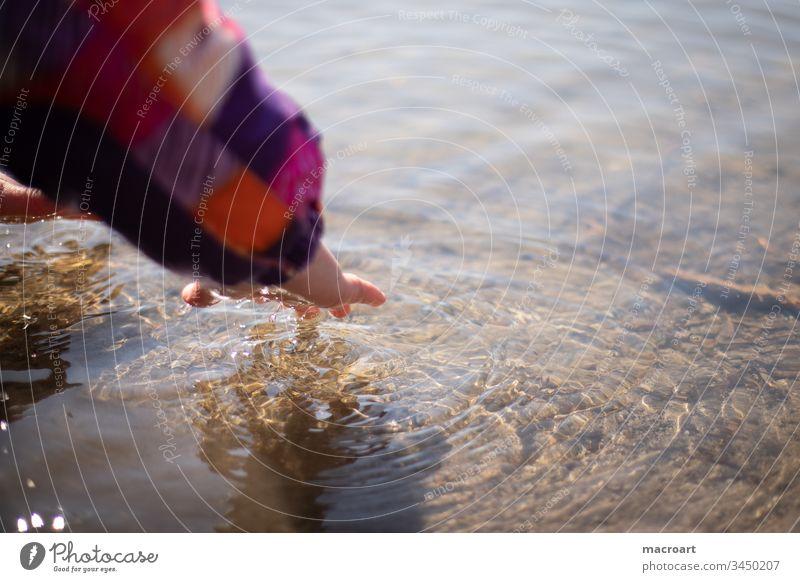 Kind spielt mit Wasser kind mädchen wasser wellen hand entdecken neugierde neugierig spielerisch lernen kalt käälte frühling gewässer kindheit unbeschwert
