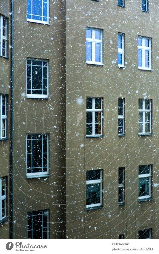 Schneefall im Hinterhof altbau außen fassade fenster haus hinterhaus hinterhof innenhof innenstadt mehrfamilienhaus menschenleer mietshaus schnee schneefall