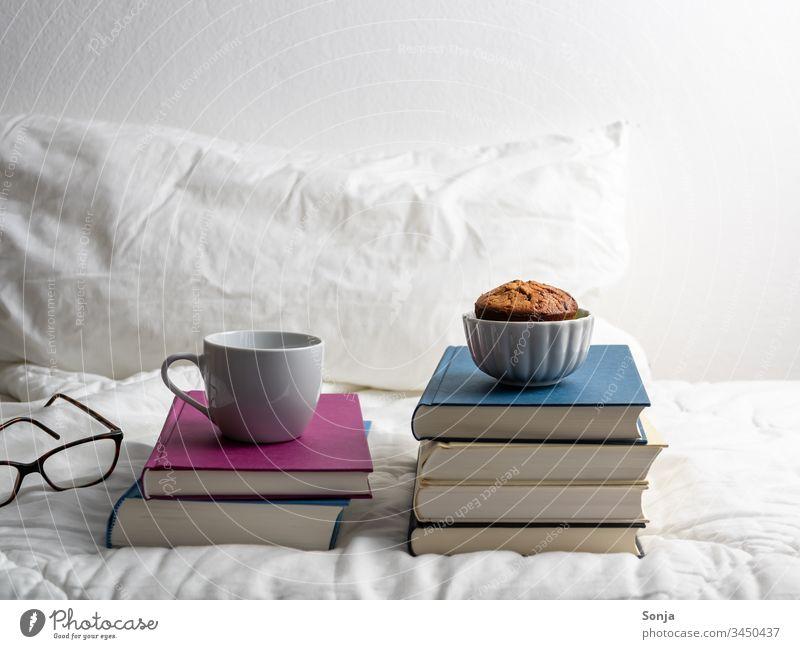 Bücherstapel mit einer Tasse Kaffee und einem Muffin auf einer weißen Bettdecke im Schlafzimmer bücherstapel Hygge bettwäsche weiss schlafzimmer vereinzelt