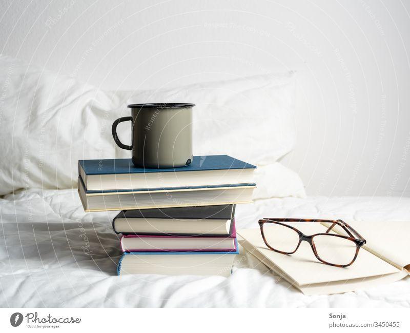 Bücherstapel mit einer Tasse Kaffee und einer Lesebrille auf einer weißen Bettdecke im Schlafzimmer bücherstapel getränk lesebrille bettdecke weiss schlafzimmer